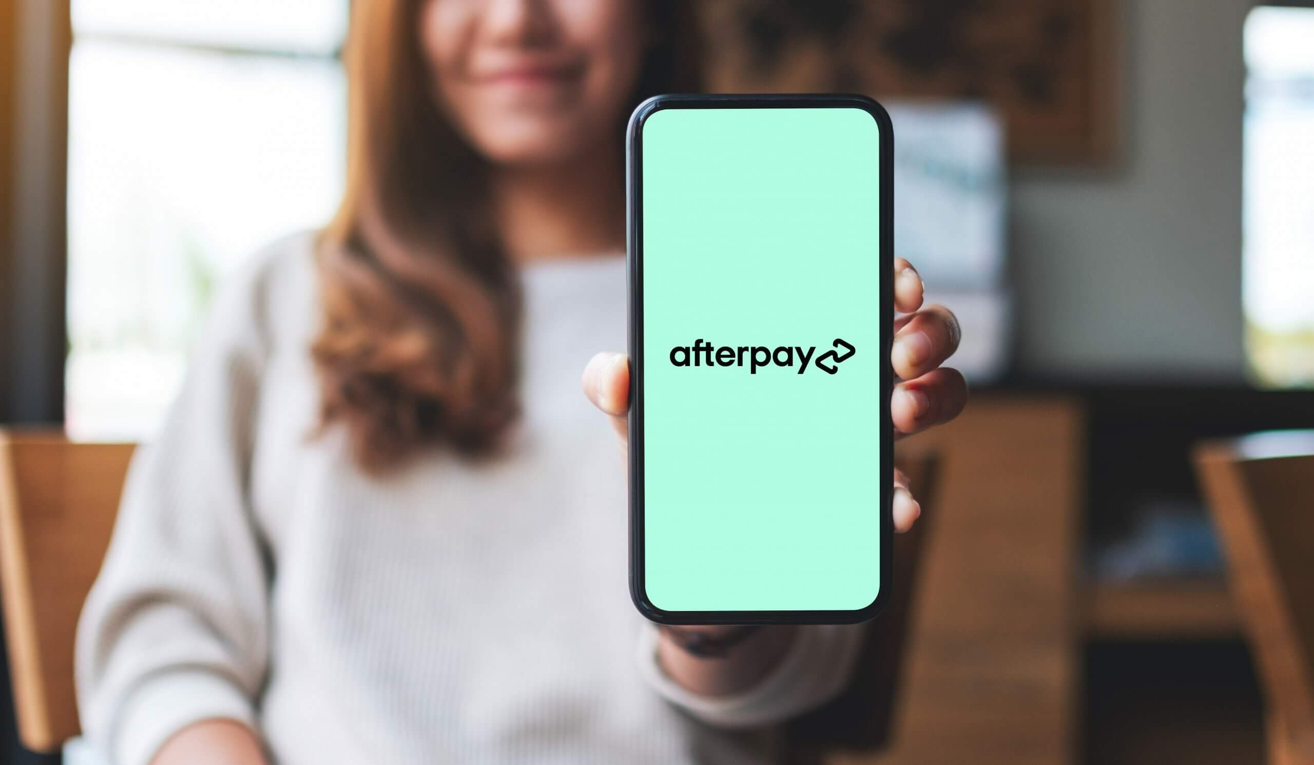 Afterpay logo holding phone scaled